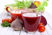 Glasses of beet juice with vegetables on wooden table closeup