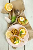 Sandwiches with green peas paste and boiled egg on plate with napkin on color wooden planks background