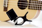 foto of ukulele  - Closeup Clip tuner Equipment For tuning the ukulele guitar sound - JPG