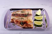 foto of pangasius  - Dish of Pangasius fillet with rosemary and lime on metal tray and color wooden table background - JPG