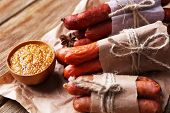 Assortment of thin sausages, and spices on paper, on wooden background