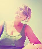 a cute girl smiling at the camera on a bright sunny day done with a retro vintage instagram filter