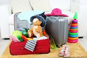 Suitcases packed with clothes and child toys on fur rug and white sofa background