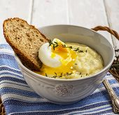 Thick mashed potatoes with poached egg and a slice of bread thyme