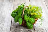 image of wooden basket  - green herbs in wicker basket on wooden background  - JPG