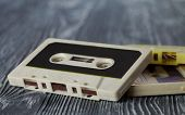 Retro Audio Cassette On The Gray Wooden Background. Vintage Paper Toning, Retro Style. Soft Focus.
