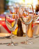Hotel Service: Table In A Restaurant With Tablecloth, Red Napkins, Wine Glasses And Cutlery. (soft F