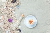 Cup, Bottle And Net With Shells On Sand