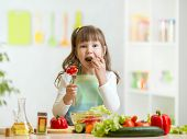 stock photo of healthy eating girl  - kid girl eating healthy vegetables at kitchen - JPG