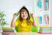 preschooler  kid girl with book over her head