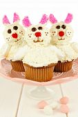 stock photo of cake stand  - Group of fun Easter bunny cupcakes on a cake stand against white wood - JPG