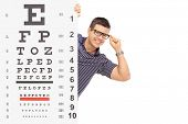 Man with glasses posing behind an eyesight test isolated on white background