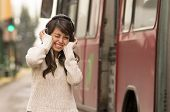 woman walking on the city street covering her ears concept of noise pollution
