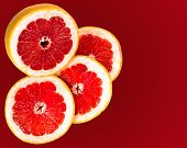 Fresh Grapefruit And Slices Isolated On A Gradient Red