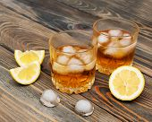 stock photo of scotch  - Glass with Scotch and ice on old wooden background