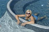 image of prone  - High angle view of aged woman that is lying prone in bright blue water of swimming pool - JPG