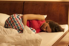 stock photo of suffering  - Woman suffering from depression sleeping in bed - JPG