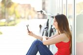 stock photo of beside  - Happy girl sitting using a mobile phone in a park beside her bicycle - JPG