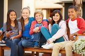 foto of pre-adolescent child  - Group Of Children Sitting On Bench In Mall - JPG