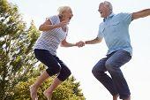 stock photo of bouncing  - Senior Couple Bouncing On Trampoline In Garden - JPG