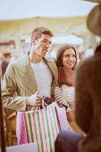 picture of mall  - Young happy couple in shopping passes in front of window shopping mall carrying bags in their hands looking in shop window - JPG