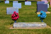pic of manicured lawn  - Colorful headstones with flowers and a manicured lawn taken at a cemetery - JPG