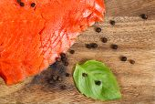 foto of peppercorns  - Close up of thinly sliced cold smoked red salmon on wooden server board with basil leafs and black peppercorn - JPG