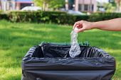picture of throw up  - Close up hand throwing empty plastic bottle into the trash - JPG