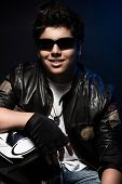 picture of biker  - Portrait of beautiful smiling teen boy biker over dark blue background - JPG