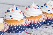 stock photo of sprinkling  - Cupcakes with patriotic sprinkles on vintage background - JPG