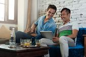 stock photo of internet-cafe  - Two Men Using Tablet Computer at Cafe - JPG