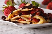 foto of crepes  - Beautiful crepes with fresh strawberries and chocolate topping close - JPG