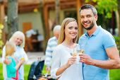 stock photo of family bonding  - Happy young couple bonding to each other and holding wine glasses while other members of family barbecuing food in the background - JPG