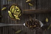 image of cardamom  - Old spoons full of cardamom and cloves - JPG