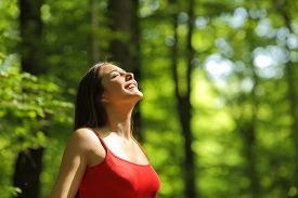 foto of breathing exercise  - Woman breathing fresh air in a green forest in summer wearing a red shirt - JPG