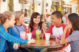 foto of pre-adolescent child  - Group Of Children Hanging Out Together In Caf - JPG