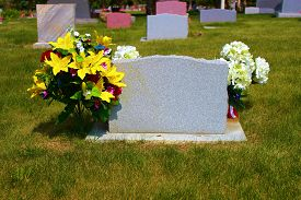 image of headstones  - Old historical headstones with flowers taken at a well maintained cemetery with a lush green lawn - JPG