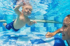 image of child development  - Portrait of child swimming with fun underwater in pool with diving cheerful mother - JPG