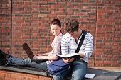 Two students working together with book and laptop outside in the campus of their university