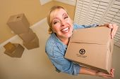 Excited Woman Holding Moving Boxes in Empty Room Taken with Extreme Wide Angle Lens.