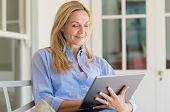 Portrait of a business woman using digital tablet in open air porch. Portrait of mature happy woman  poster