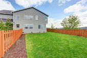 Spacious Fenced Back Yard With Green Grass. House Exterior Of A Large House. poster