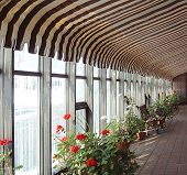 stock photo of awning  - Greenhouse like hallway in winter with blooms inside and icicles on outside windows - JPG