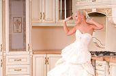 Bride Stands In The Kitchen And Laughs