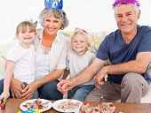 stock photo of birthday party  - Happy family looking at the camera on a birthday - JPG