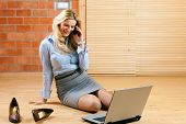 Business woman working at home with her laptop on the floor and makes a phone call