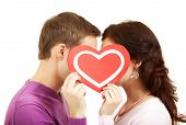 stock photo of corazon  - Two young people kissing behind a paper heart - JPG
