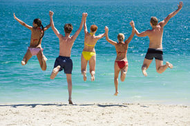image of beach holiday  - Portrait of five teens jumping into lake simultaneously holding each other by hands - JPG