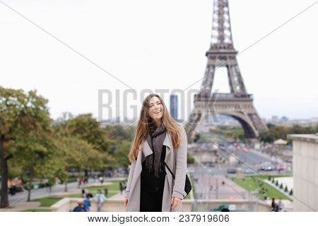 poster of Young Female Person In Grey Coat Standing With Eiffel Tower Background In Paris. Concept Of Travelin