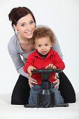 Постер, плакат: Женщина и ребенок играя с игрушкой рулевое колесо